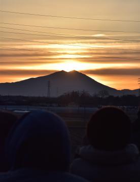曇りがかった空から昇る朝日を眺める参加者=12日午前7時5分、結城市結城