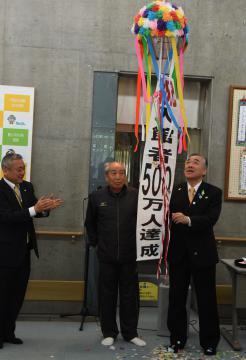 500万人目の入館者となり、くす玉を割った中河昇さん(中央)と須藤茂市長(右)=筑西市新井新田のあけの元気館