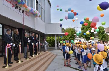 豊田稔市長や石井竜也さんらのテープカットに合わせて小学生が風船を飛ばして開館を祝った=北茨城市関本町富士ケ丘