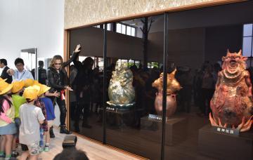 ギャラリーに展示した作品を小学生に説明する石井竜也さん=北茨城市関本町富士ケ丘