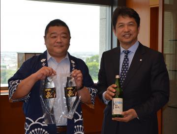 吉久保酒造の吉久保博之社長(左)が日本酒「サバデシュ」をPR=県庁