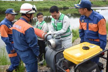筑西広域消防本部の協力で、排水ポンプの操作訓練を行う筑西市職員ら=筑西市岡芹