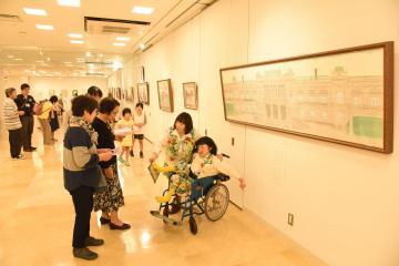 文字ボードを足で指し示しながら来場者に作品の解説をする渡辺良子さん(右)=筑西市スピカ庁舎多目的スペース