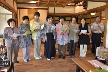 鈴木一覚さん(右)の尺八の伴奏で練習に励む会員たち=桜川市内