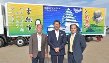 トラックの前に立つ(左から)トランスシグマの野崎真宏会長、神達岳志市長、野崎真史社長=常総市馬場