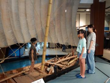 かすみがうら市歴史博物館で帆引き舟の模型を見学する親子=かすみがうら市坂