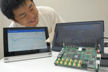 データ圧縮モジュールを組み込んだ試作ボードを確認する山際伸一社長=つくば市松代