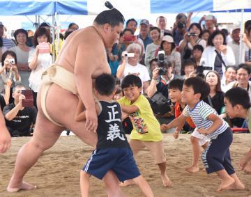 ナシと相撲の祭典「第29回どすこいペア」で、御嶽海関に挑む子どもたち=筑西市舟生
