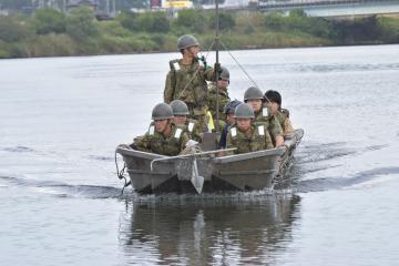 水害と地震の複合災害を想定した訓練で、ボートによる住民の救助に臨む隊員=ひたちなか市枝川