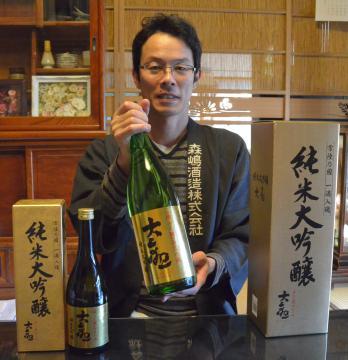 日本航空国内線ファーストクラスで今月提供されている「大観 純米大吟醸」を手にする森嶋正一郎専務=日立市川尻町