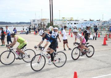 土浦新港でスイムを終えバイクのスタートを切る参加者=土浦市川口