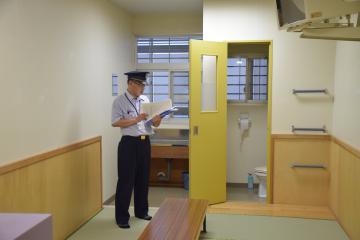 収容者の居室で間取りなどを説明する東日本入国管理センターの職員=5月23日午前、牛久市久野町