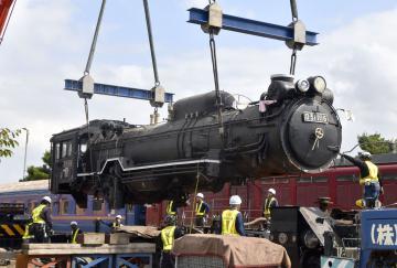 寝台列車「北斗星」の隣で設置作業が進められる、蒸気機関車(SL)のD51形。搬送は三つに分解して行われた=筑西市のザ・ヒロサワ・シティ