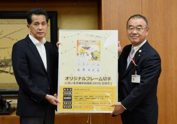 山口伸樹市長(左)にオリジナルフレーム切手の見本を贈呈する小松直之副統括局長=笠間市中央