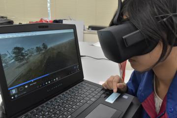 鬼怒川決壊の様子を再現したVR映像を専用ゴーグルで見る国交省職員=同省下館河川事務所