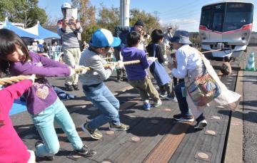 車両の綱引きに挑戦する子どもたち=つくばみらい市筒戸のTX総合基地