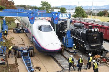 パワーリフトを用いて設置作業が進められている新幹線車両「E224-127」。右隣は蒸気機関車のD51=筑西市のザ・ヒロサワ・シティ
