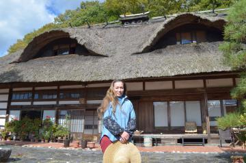 父クナッパーさんが愛した茅葺き屋根の自宅前に立つ長女のウテさん=大子町塙
