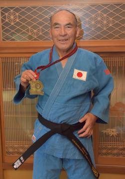 世界大会優勝の金メダルと、副賞の「チャンピオン帯」を身に着けて笑顔を見せる羽生利彦さん=行方市荒宿