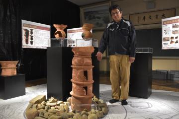 「朝顔形円筒埴輪」の前で、企画展への来場を呼び掛ける蓼沼香未由さん=大洗町大貫町