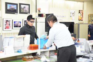 防犯訓練で強盗犯役(左)に現金を要求され、対応する結城信金職員=筑西市丙の結城信金下館支店