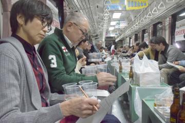真剣な表情で利き酒に挑戦する参加者=ひたちなか海浜鉄道湊線