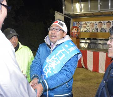 初当選を決め、支持者と握手を交わす石塚隼人氏=坂東市弓田