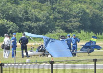 墜落した超軽量飛行機を調べる水戸署員ら=7月14日、水戸市元石川町