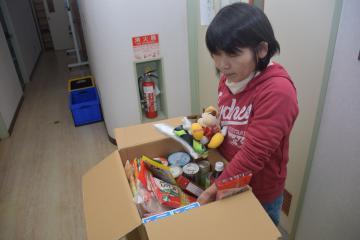 段ボール箱に食品や縫いぐるみなどを入れるNPO法人「NGO未来の子どもネットワーク」のメンバー=龍ケ崎市