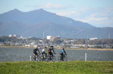 筑波山方面に向かい、霞ケ浦湖畔をサイクリングする人たち=2018年10月、土浦市内