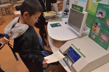 本を借り、「本の通帳」を機械に入れて記帳する子どもたち=土浦市立図書館