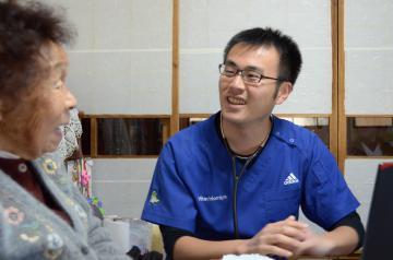 訪問診療先で患者の女性と談笑する小田有哉医師=常陸大宮市内