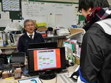 田村俊之教頭(左)が開発した勤務時間記録システムを使い、退勤を記録する教職員=古河市小堤の総和北中