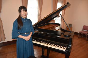 CD制作で使用したスタインウェイ社製のピアノの前に立つ石塚美咲さん=水戸市緑町