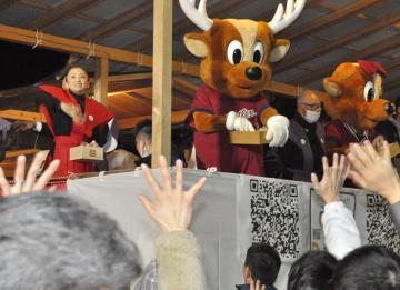 鹿島神宮の節分祭で豆をまく女優の永作博美さん(左)や鹿島アントラーズのマスコット=鹿嶋市宮中