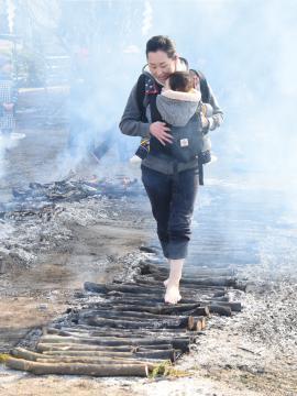 無病息災を祈願し、子どもを抱いてはだしで「火の道」を歩く女性=筑西市辻