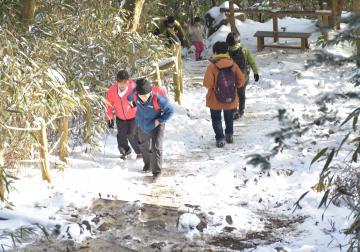 雪景色となった山道を歩く登山者=10日午後、筑波山山頂付近
