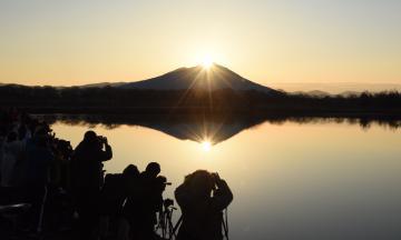 筑波山頂に現れた朝日「ダイヤモンド筑波」と、母子島遊水地に集まったカメラマンら=14日午前6時55分ごろ、筑西市飯田