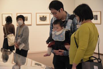 色彩豊かな展示作品をじっと見つめる8カ月の赤ちゃん=水戸市千波町