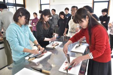 魚さばき体験に挑戦する大学生=北茨城市関南町