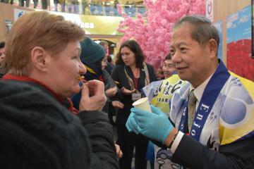 磯崎久喜雄団長(右)から干し芋を受け取り、試食するロシア人の女性=モスクワ