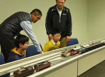 定例運転会で鉄道模型に見入る、下館レイル倶楽部の飯島成彦会長(右奥)や子どもたち=筑西市丙