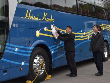 「Heisei Kanko」と社名が入ったバスを磨く平成観光自動車の運転手と従業員=龍ケ崎市泉町