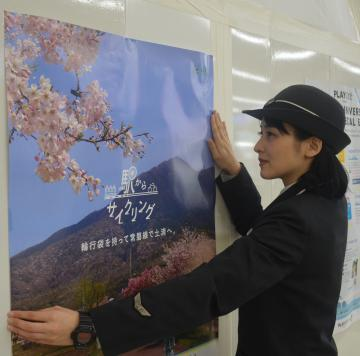 輪行袋推奨のポスターを貼るJR東日本社員=土浦市有明町のJR土浦駅