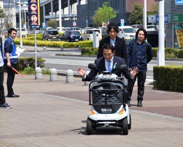 自動運転する電動車椅子に試乗する五十嵐立青市長=つくば市研究学園のTX研究学園駅前