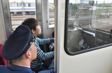 運転士に教わりながら気動車を運転する小学生=常総市水海道高野町