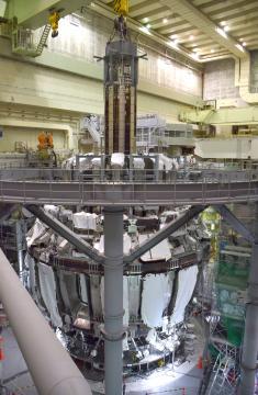超伝導トカマク型核融合実験装置「JT-60SA」の中心部に巨大な磁場コイルを挿入する作業=那珂市向山