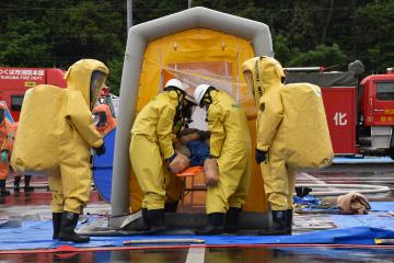 化学防護服姿で重症者の救助訓練を行う機動隊員ら=20日、つくば市高野