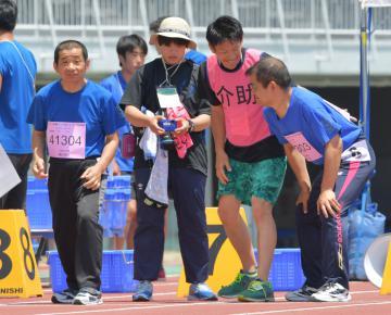 50メートル走に出場する選手に声を掛ける介助スタッフ=笠松運動公園陸上競技場、鹿嶋栄寿撮影