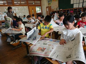 新聞をめくって気になる記事を探す児童たち=那珂市立瓜連小